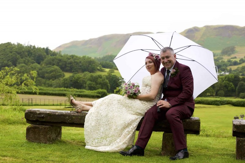 bride and groom seated on a garden bench under an umbrella. Mountains are in the background