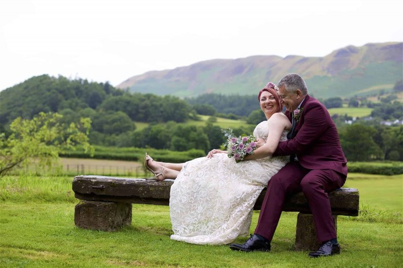 bride and groom seated on a garden bench in the lake district. Mountains are in the background