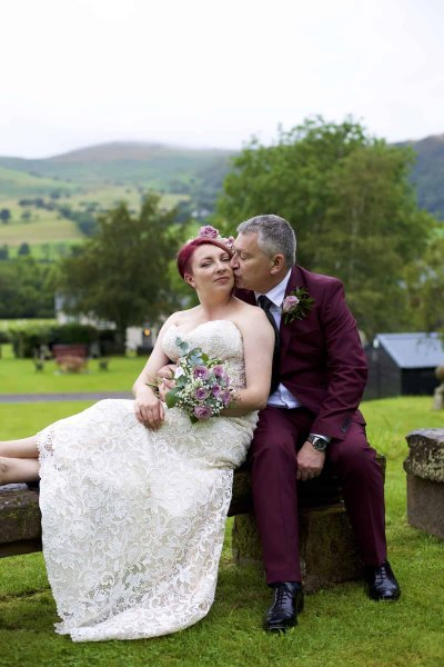 bride and groom kissing on a garden bench in the lake district. Mountains are in the background