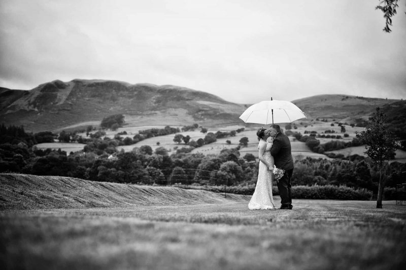 black and white wedding photograph of a couple kissing under an umbrella in the lake district