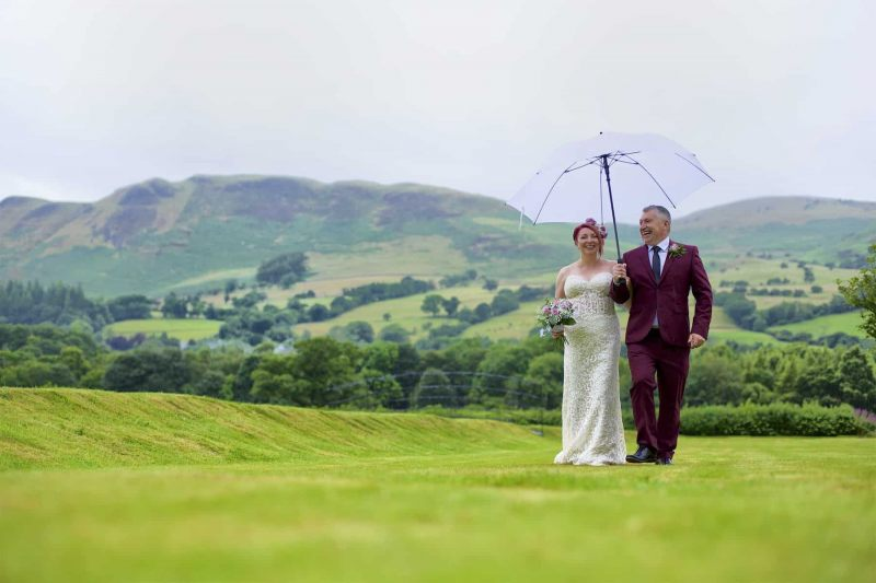 bride and groom walking in a lake district garden laughing under an umbrella