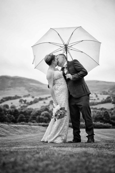black and white photograph of a bride and groom kissing under an umbrella in the lake district