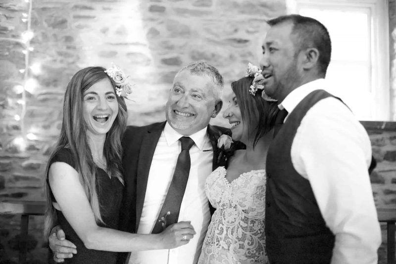bride and groom laughing with friends