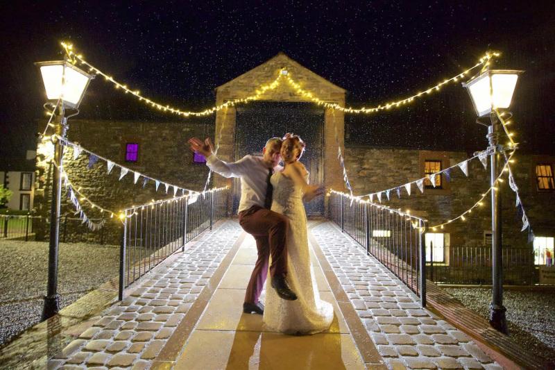 bride and groom dancing in the rain