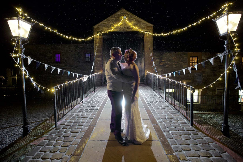 bride and groom kissing in the rain at night