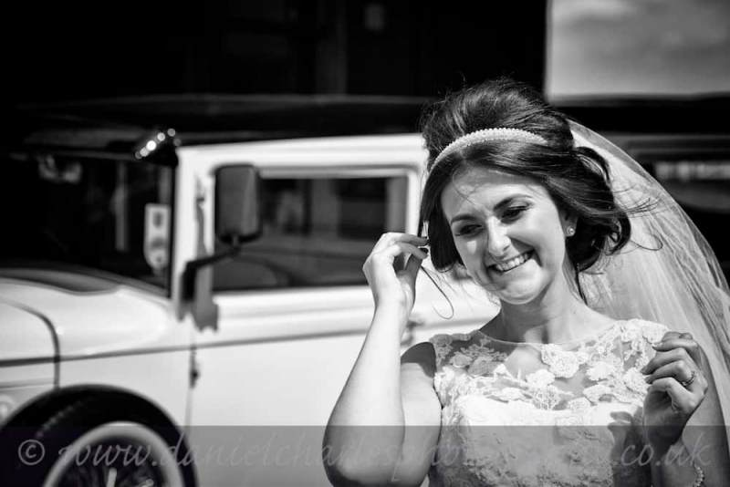 black and white image of bride standing beside wedding car at aintree racecourse