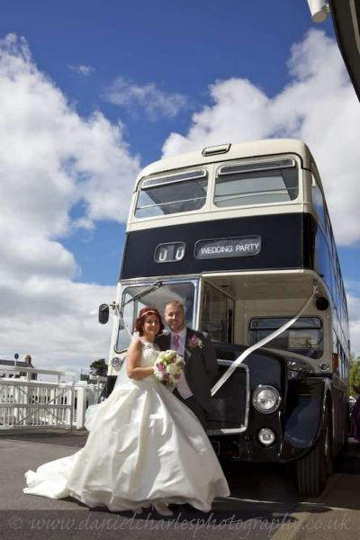 bride and groom standing together in front of wedding bus
