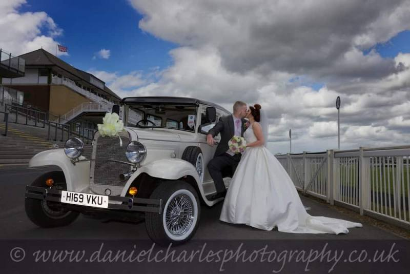 bride and groom standing by wedding car with big sky