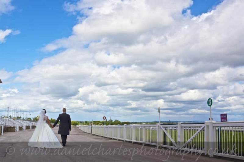 wide angle shot of bride and groom walking under big cloudy sky