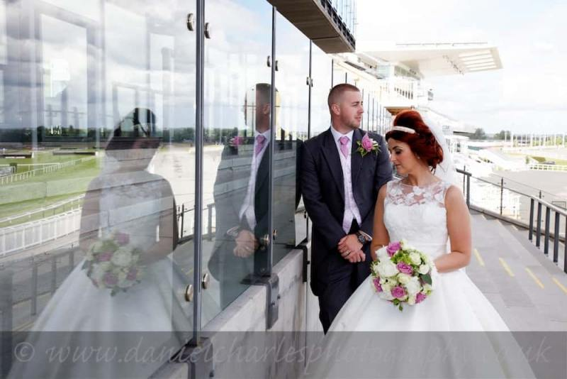 Bride and groom standing by reflective glass