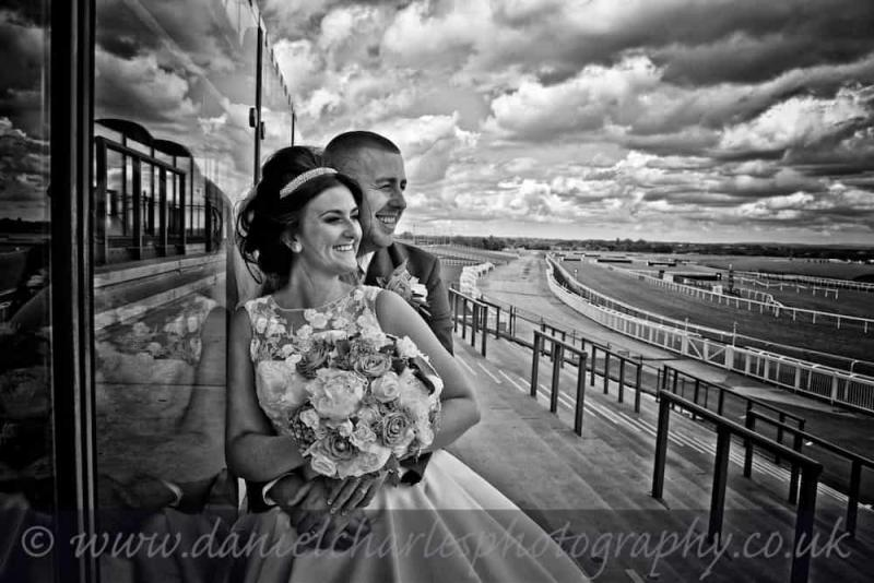 bride and groom looking over racecourse black and white wedding photography