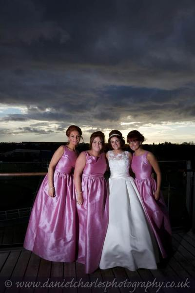 bride and bridesmaids photographed against cloudy sunset sky