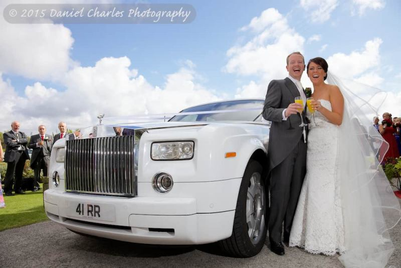 bride and groom laughing as they share a drink by their wedding car leasowe castle