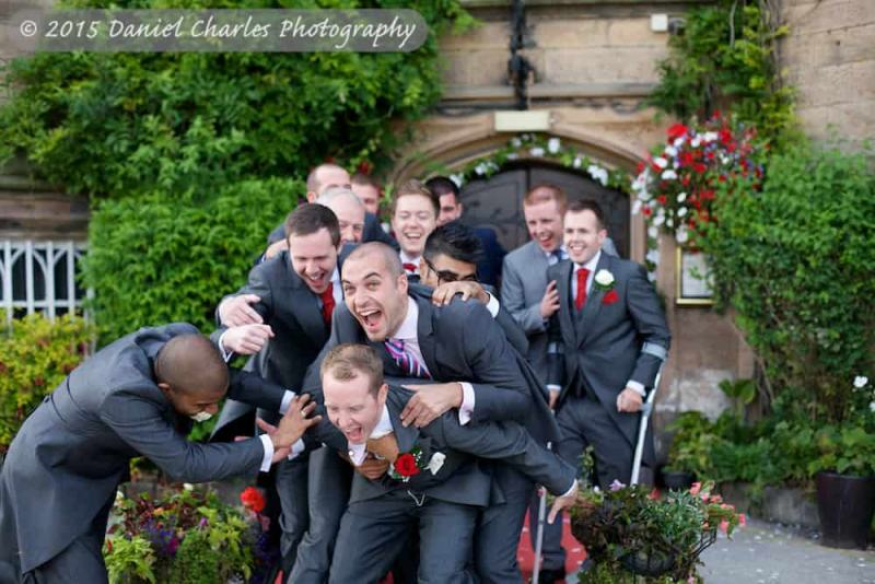 groomsmen jumping on the groom outside leasowe castle wirral wedding photographer daniel charles photography