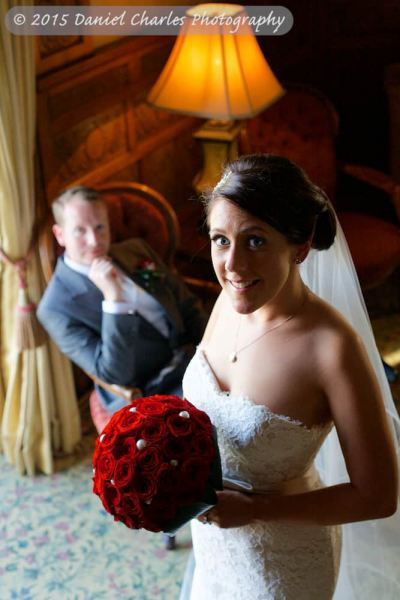 bride looking up at camera with groom seated in background