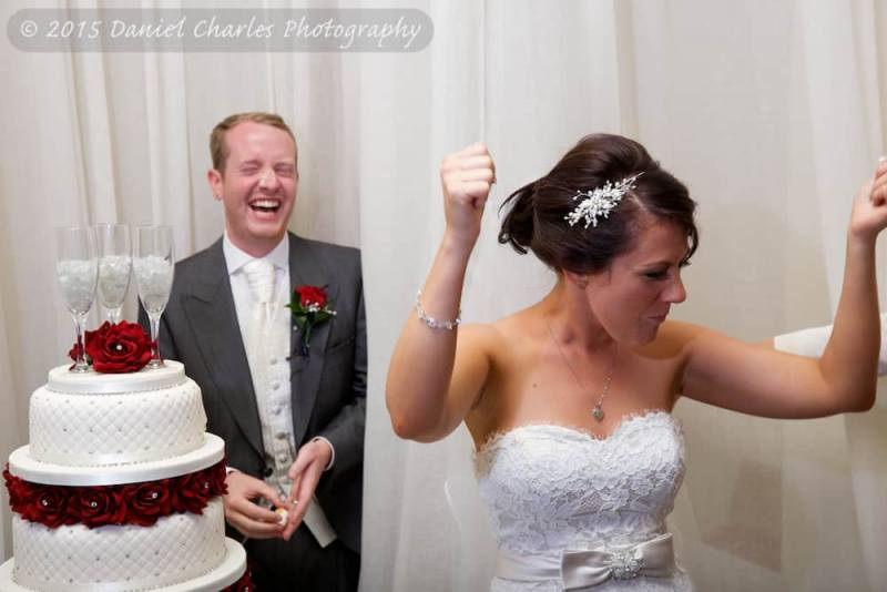 bride celebrating after putting cake into groom's face - groom is laughing
