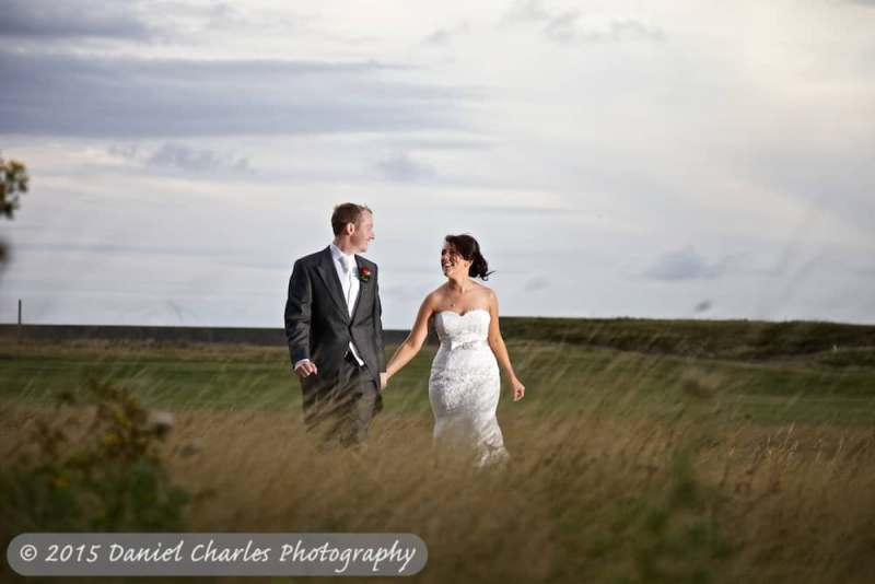 bride and groom walking through wirral meadow