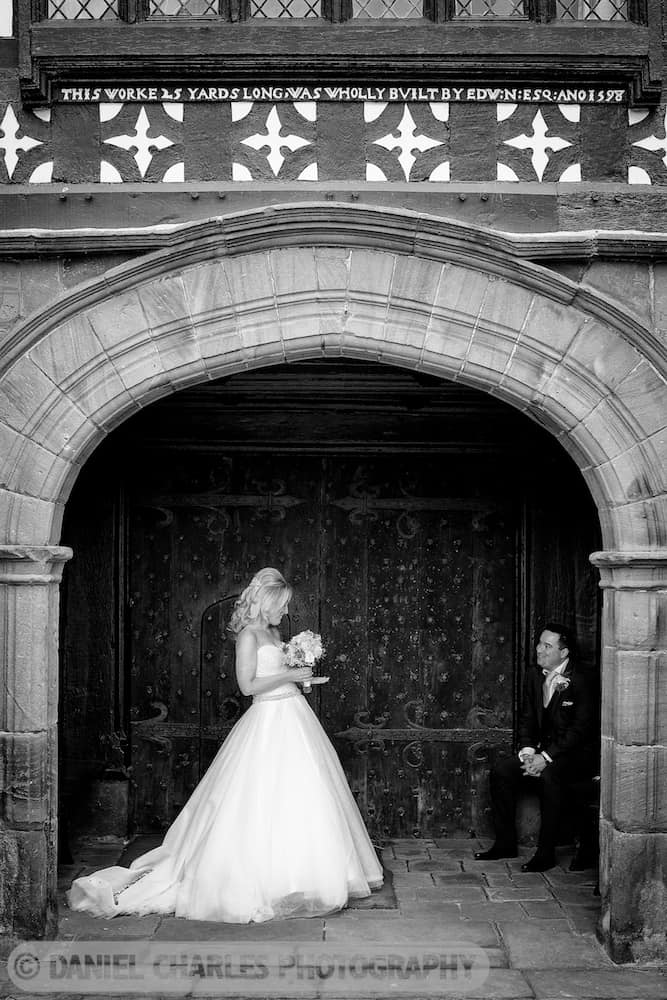 The groom is seated in the doorway of Speke Hall. The bride is looking on. This photo is black & white.
