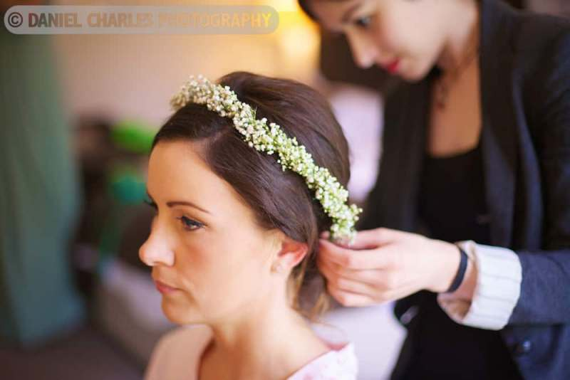 hairdresser fixing floral garland to bride\'s hair