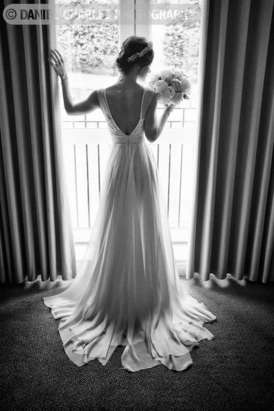 black and white wedding portrait of bride\'s dress from behind.