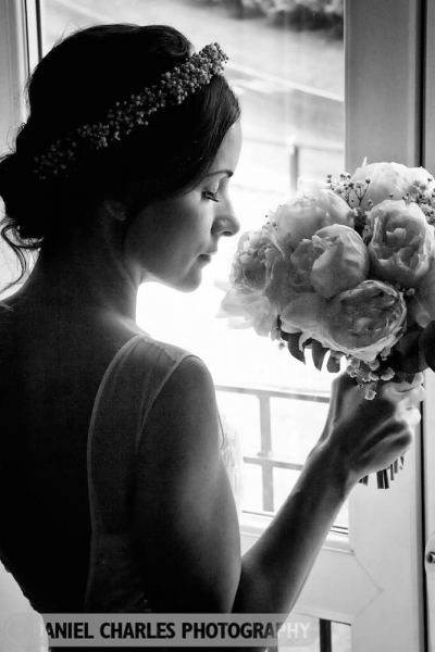 black and white wedding portrait of bride smelling  her flowers