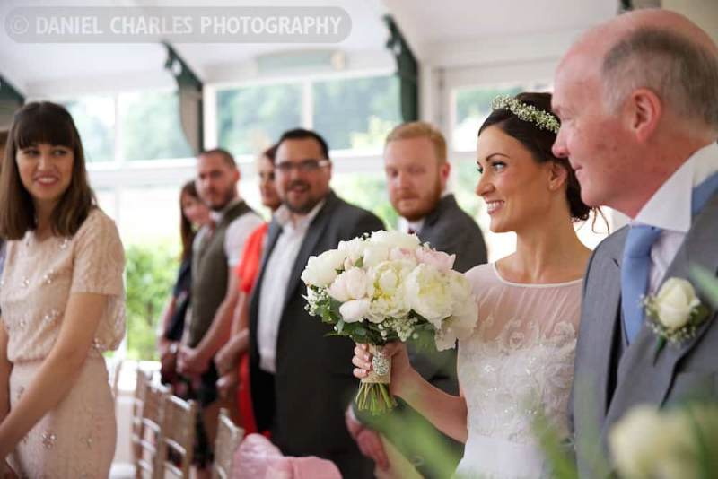 the bride catches the groom\'s eye as she walks the aisle with her dad
