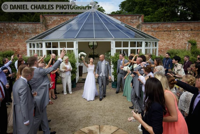 bride and groom and confetti outside combermere abbey glasshouse