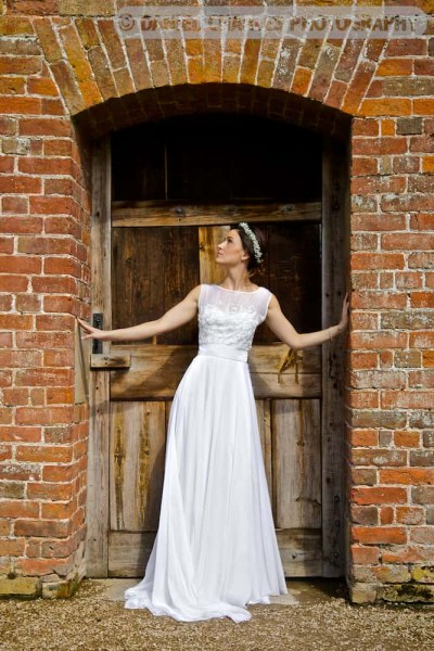 bride standing in gate alcove in combermere abbey walled gardens