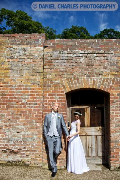 bride and groom standing by gate in walled garden of combermere abbey wedding photography by daniel charles photography