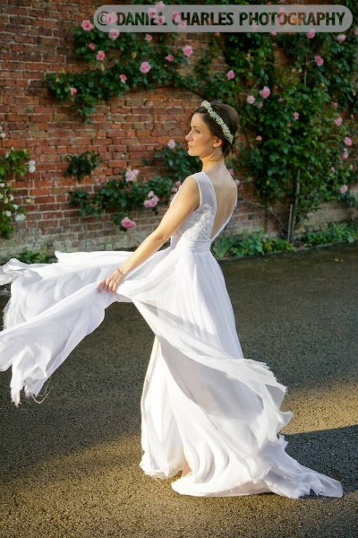 Bride swishing wedding dress at combermere abbey walled garden