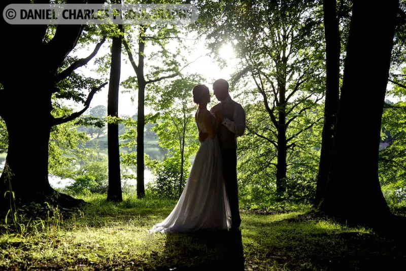 bride and groom embracing in woodland with lake in background image by cheshire wedding photographer daniel charles photography