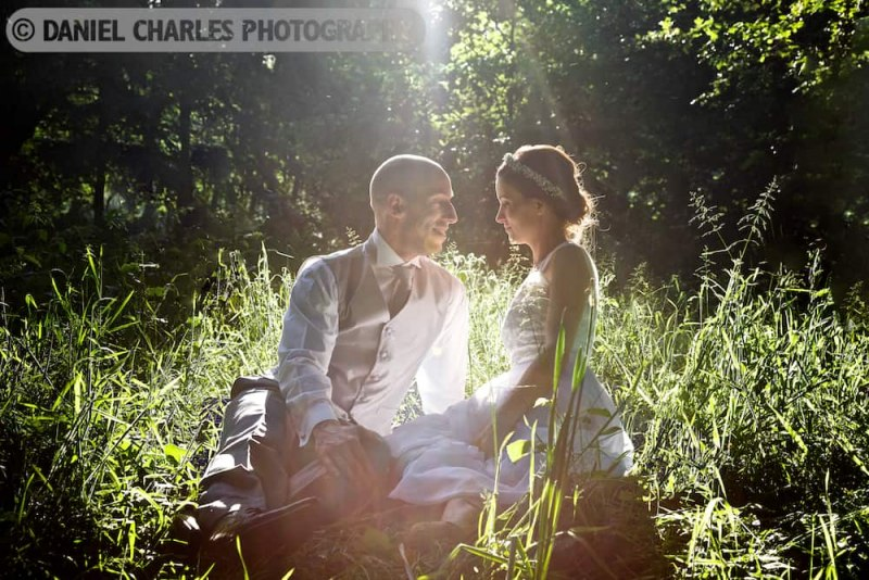 bride and groom seated in summer glade with back light streaming thorough trees