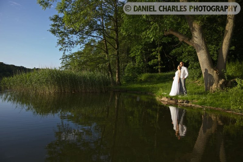 bride and groom standing by edge of lake, reflected in water.