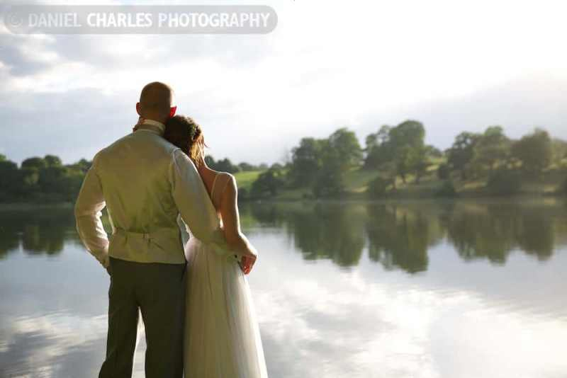 Bride and groom facing lake with reflections on waterline