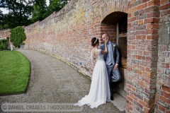 bride caresses groom\'s face in combermere abbey walled garden
