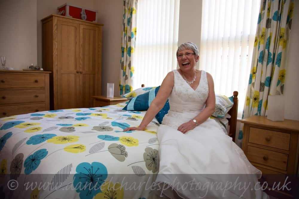 bride seated on bed laughing