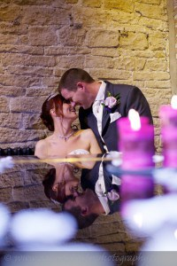 bride and groom seated by piano with strong reflections on piano lid