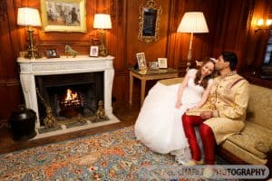 bride and groom seated on sofa with fire in fireplace thornton manor