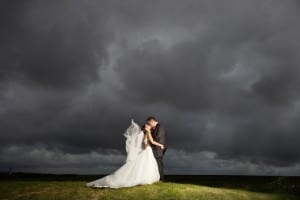 bride and groom kissing in front of stormy sky by Leasowe Castle