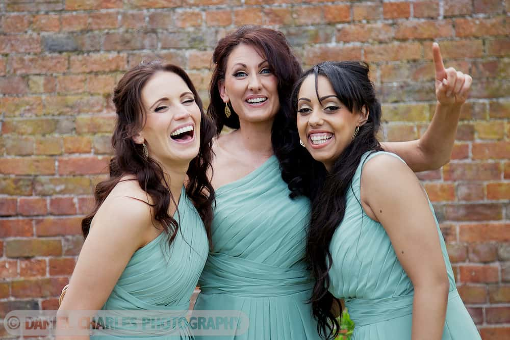 bridesmaids dressed in light green dresses laughing at camera