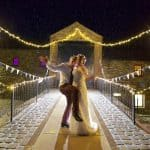 bride and groom dancing in night time rain