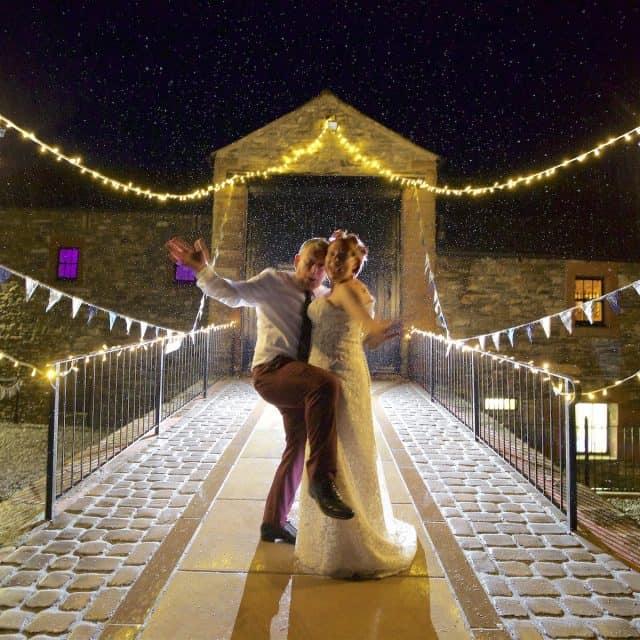 bride and groom dancing in night time rain