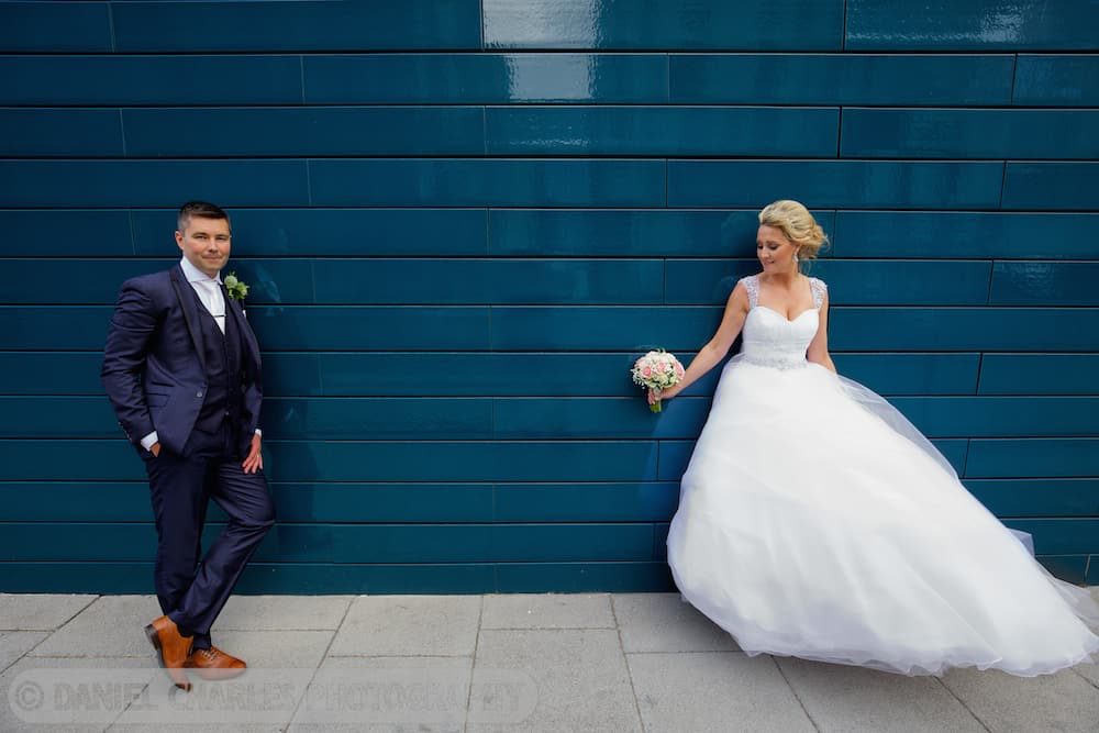 bride and groom leaning against tiled wall in liverpool