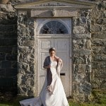 a bride adjusts her scarf standing in front of an old door at Seiont Manor Hotel