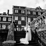 black and white image of bride and groom standing on steps at Knowsley Hall