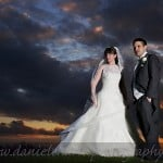 bride and groom standing against a stormy sunset sky