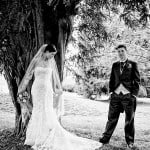bride leaning against tree while groom looks on