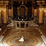 Bride and groom kiss in great hall