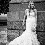 Bride leans against memorial wall