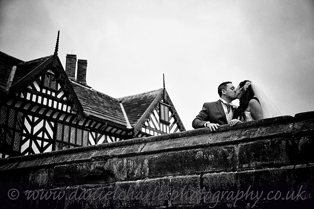Bride and groom kiss with speke hall in background